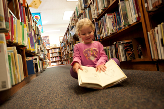 Child Looking at a Book in the Library